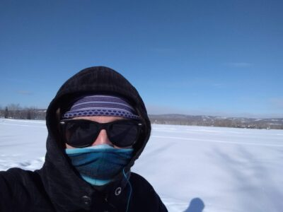 a person wearing a fleece jacket, a blue head band, sunglasses and a buff over their nose and mouth in a snowy field on a sunny winter day in Fairbanks Alaska