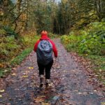 A person wearing pacific northwest winter gear on a wet hiking trail in the rain. The person is wearing rubber boots, black leggings, a red rainjacket and an orange hat as well as a backpack with a rain cover. They are walking on a gravel trail with undergrowth and trees on each side