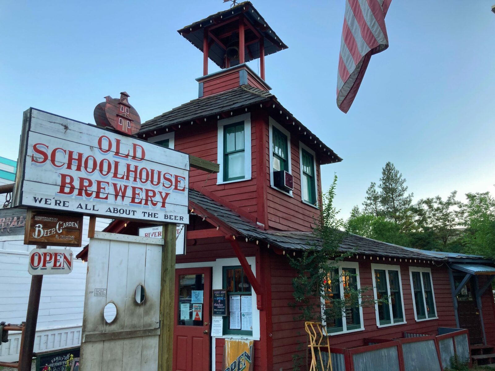 A historic tiny red schoolhouse with a sign in front that says Old Schoolhouse Brewery in Winthrop, Washington, near North Cascades National Park