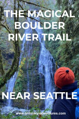 A high waterfall coming down a rock cliff surrounded by moss and ferns. There are evergreen trees in the foreground and a hiker with an orange hat looking at the waterfall. Text reads: The magical Boulder River Trail near Seattle