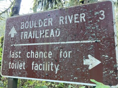 A brown national forest service sign points ahead for the boulder river trailhead in three miles and the last chance toilet facility with an arrow pointing right