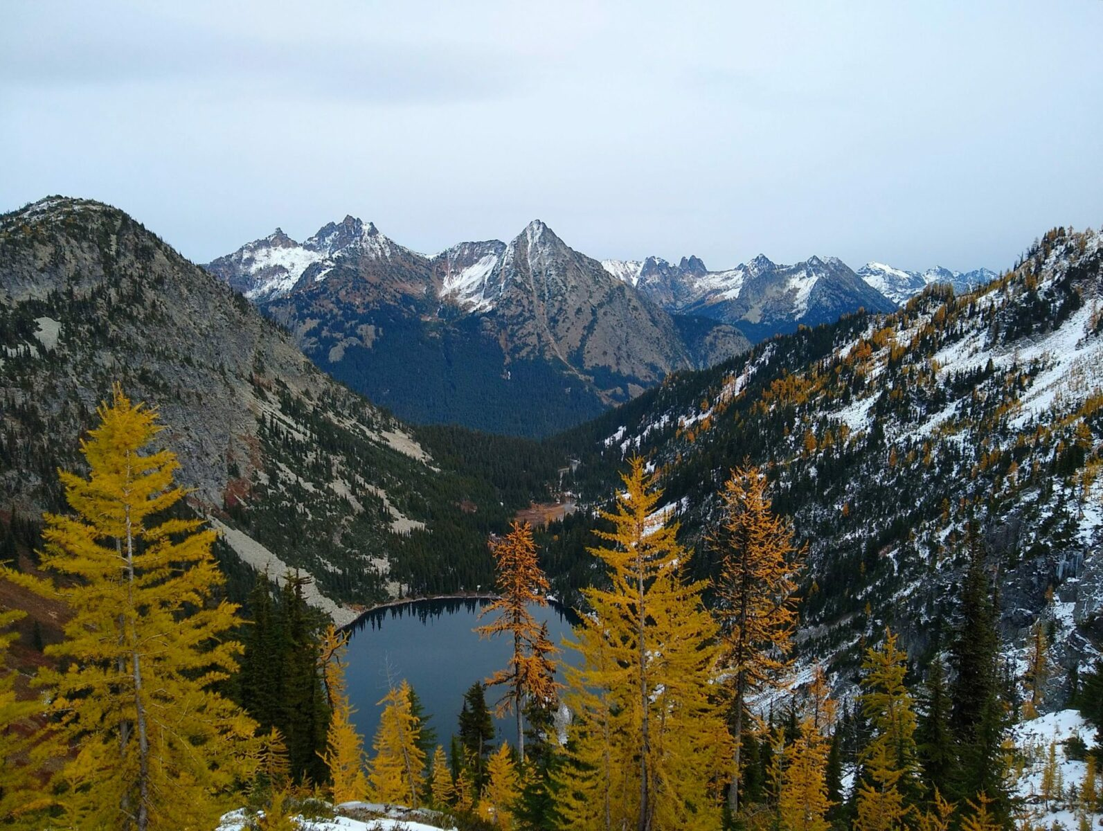 Golden larch trees in the foreground frame an alpine lake below. The lake is surrounded by high mountains with a dusting of snow. It's an overcast day along the Maple Pass trail, one of the best larch hikes in Washington