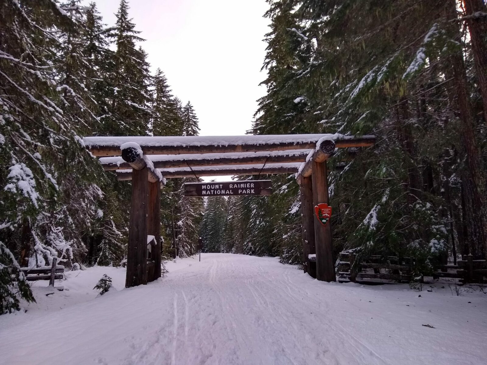 A road covered in snow surrounded by evergreen trees that are also snow covered. A wooden sign over the road says Mount Rainier National Park