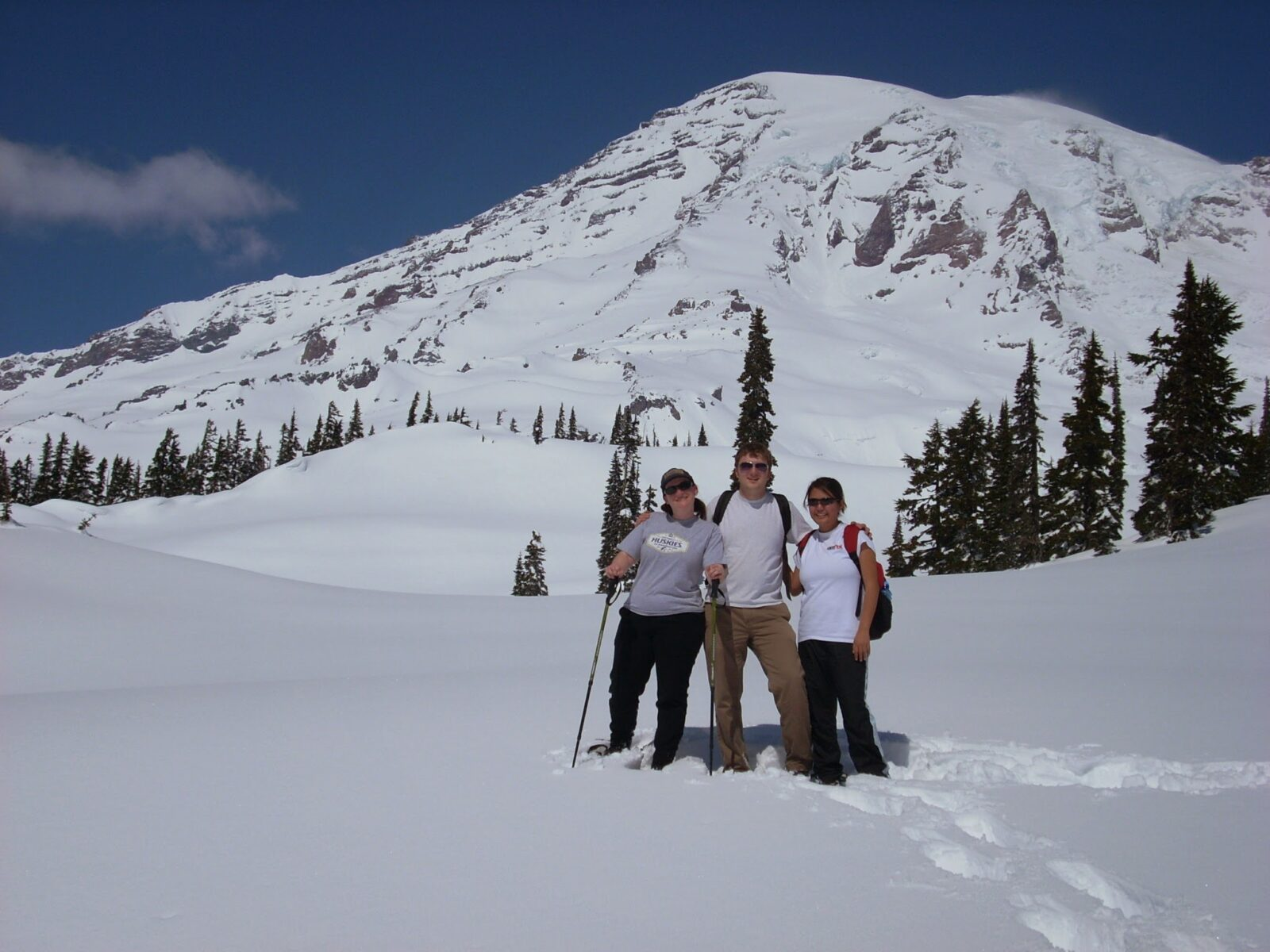 Three hikers pose for the camera in snow in front of Mt Rainier. They are wearing snowshoes, t shirts and sunglasses. Evergreen trees are visible as well.