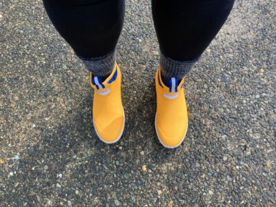 Looking down at a pair of yellow boots on a sidewalk