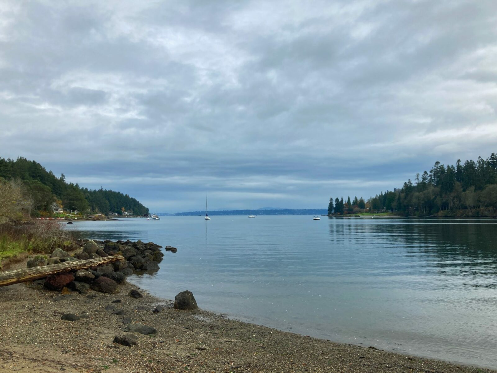 One of the hikes on bainbridge island leads from Fort Ward to the head of Blakeley Harbor in Blakeley Harbor park. The park has a rocky beach that is surrounded by evergreen trees. The harbor is shallow and narrow, with a few boats anchored in the distance.