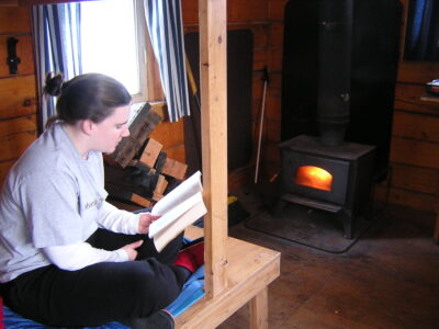 A woman sitting on a wooden bunk in a cabin near a woodstove. There are orange flames visible in the woodstove. She is reading a book