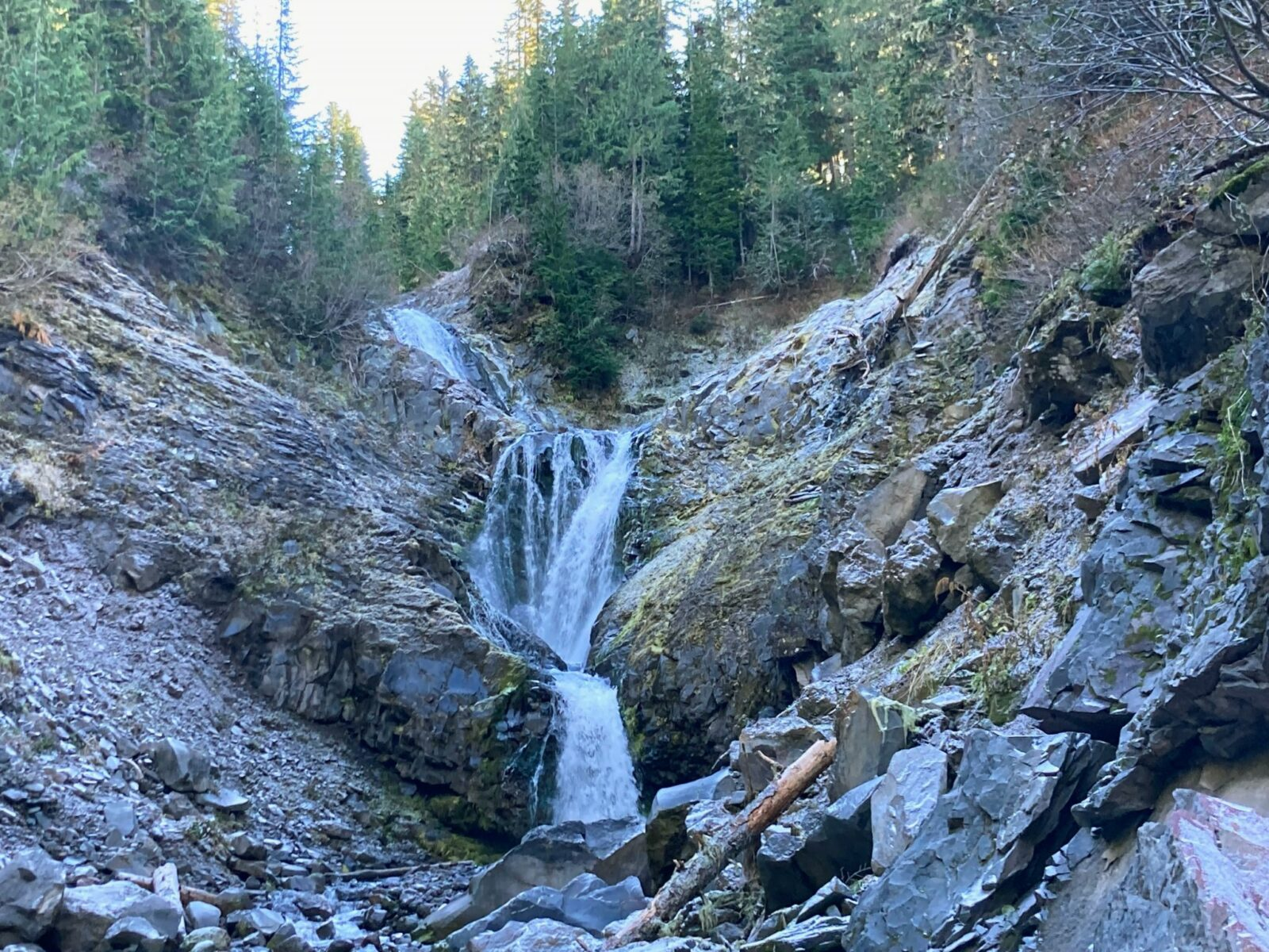 A waterfall tumbling between rocks in a ravine in the forest on the Comet Falls trail in Mt Rainier National park