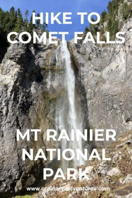 A waterfall comes down a cliff face with evergreen trees at the top of the cliff on a sunny day. Text reads: Hike to Comet Falls Mt Rainier National Park