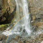 Comet Falls, a Mt Rainier waterfall, plunges onto rocks on a sunny day, creating a rainbow across the bottom of the waterfall