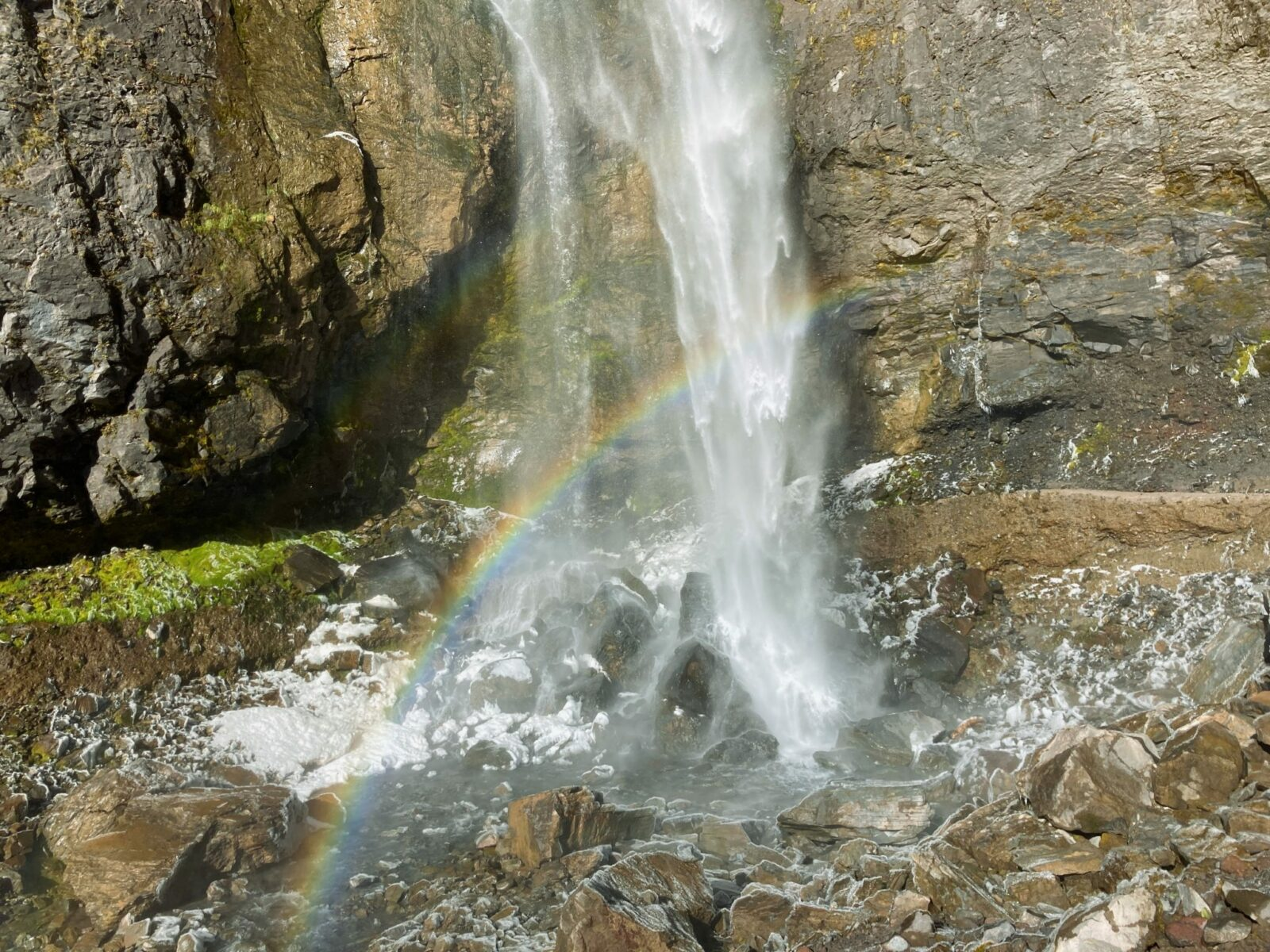 The base of Comet Falls crashes onto frosty rocks. There is also foam from the waterfall and a rainbow arcs across the base of the waterfall