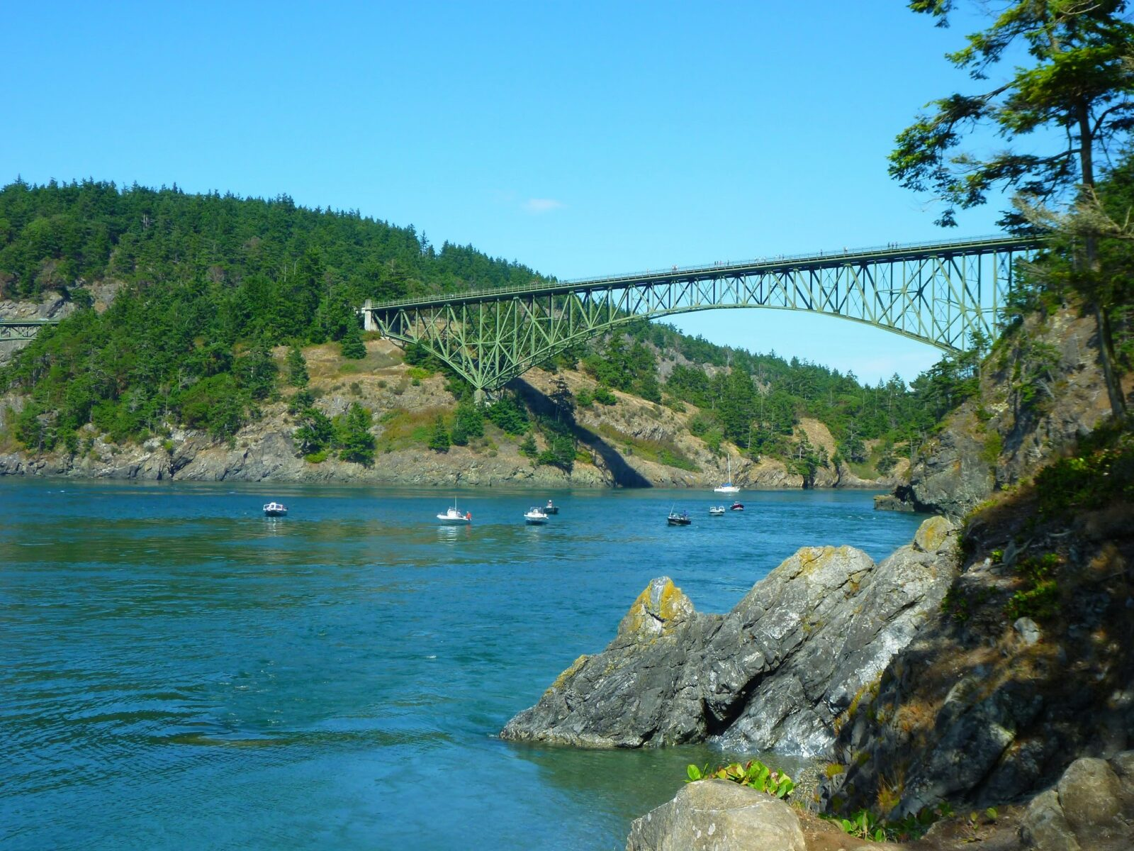 A green steel bridge is high above the water between two rocky and forested hills on each side of a narrow passage. There are a few fishing boats and one sailboat in the water under the bridge