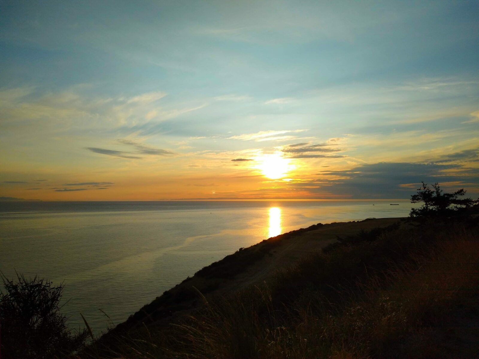 Sunset from a whidbey island hike at Fort Ebey State Park. There is a bluff in the foreground in shadow with a couple of trees. Beyond is calm water going as far as you can see. The sun is just setting behind a few clouds