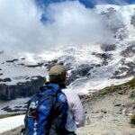 A woman with a backpack looks at mt rainier from the trail