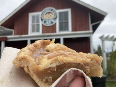 A close up of a piece of apple pie with a crust and caramel on the top. In the background is an out of focus red building