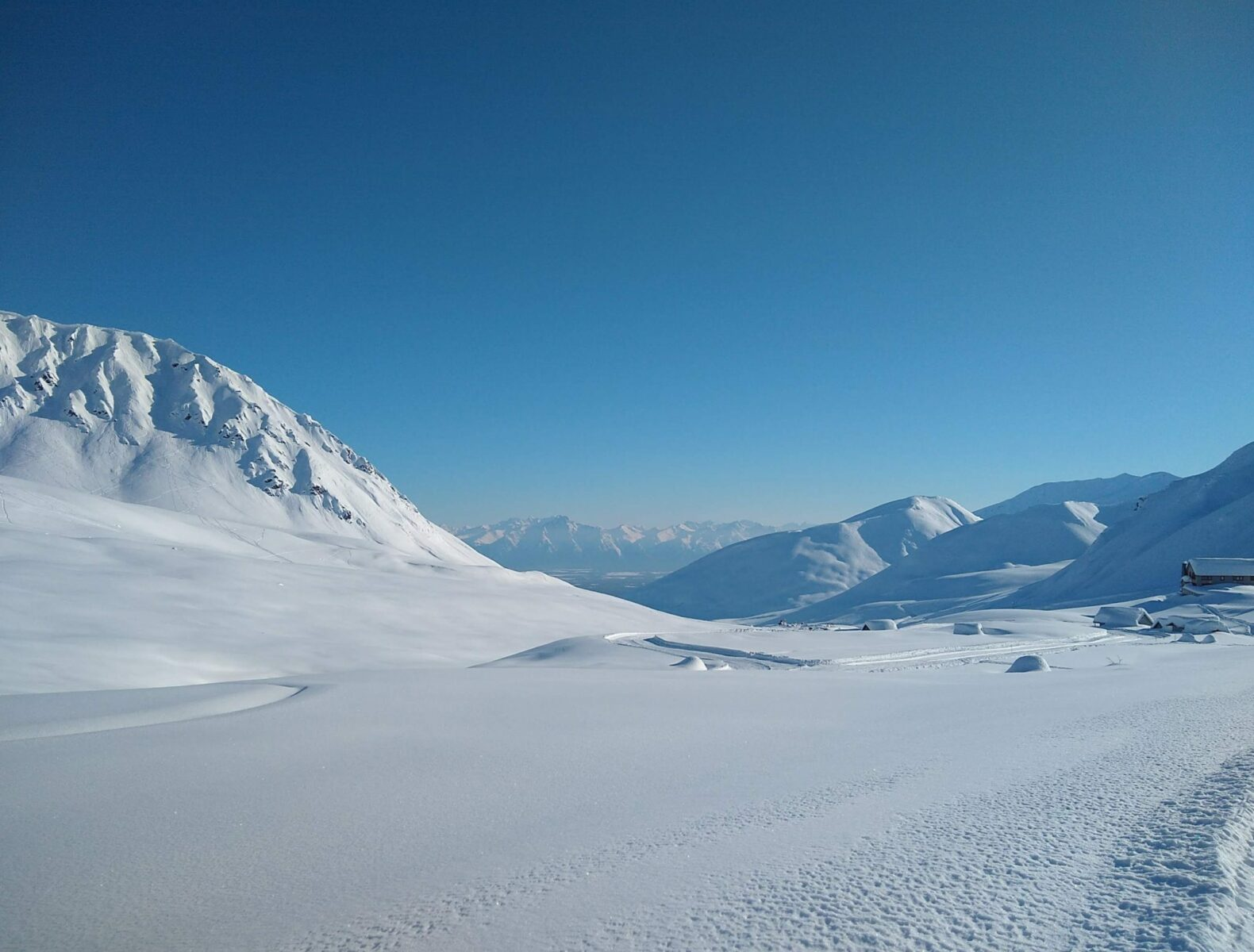 Hatcher Pass in Alaska in winter. There is a giant snowy valley surrounded by mountains on a snowy day. There are even higher mountains in the distance
