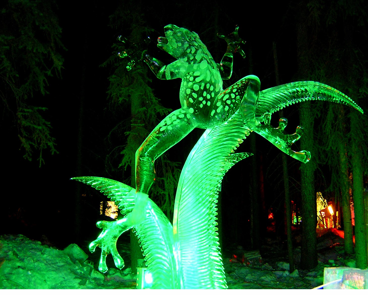 A giant frog carved from ice. It is dark and the frog is lighted in green lights.