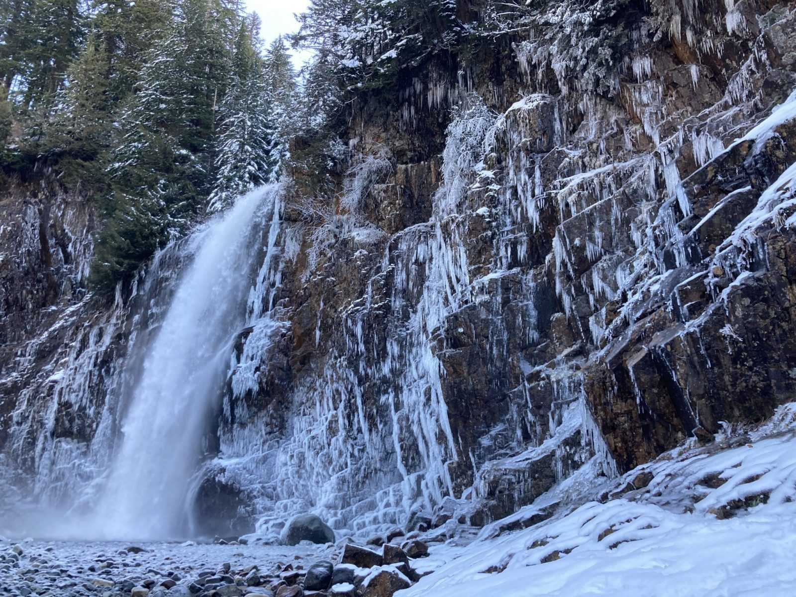 A powerful waterfall coming over a vertical rock face. The rocks are covered in icicles and the ground around the waterfall is covered in snow.
