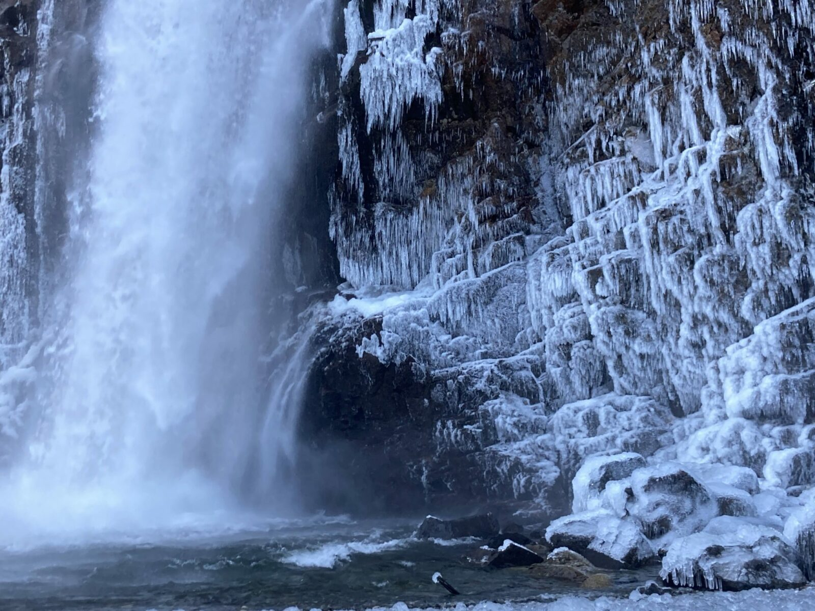 Franklin Falls in winter splashing into a pool at the base of the falls. The rocks are covered in ice and icicles around the waterfall base