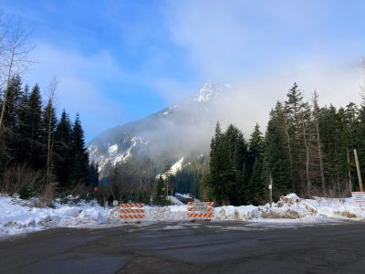 Road closed barricades in front of a snow berm on a closed road. In the distance is a mountain partly covered by fog and there are evergreen trees in the foreground.