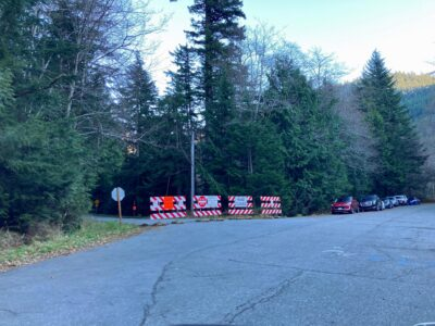 Closed road signs across a road where you park to hike Franklin Falls in winter from the Denny Creek side. There are cars parked along the road and trees around the road.