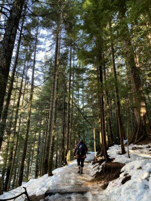 A hiker walking on the trail to Franklin Falls in winter. There is packed ice on the trail and it is surrounded by evergreen trees. The hiker is wearing a blue and green hat, a brown down coat, black leggings, rubber boots and a blue backpack