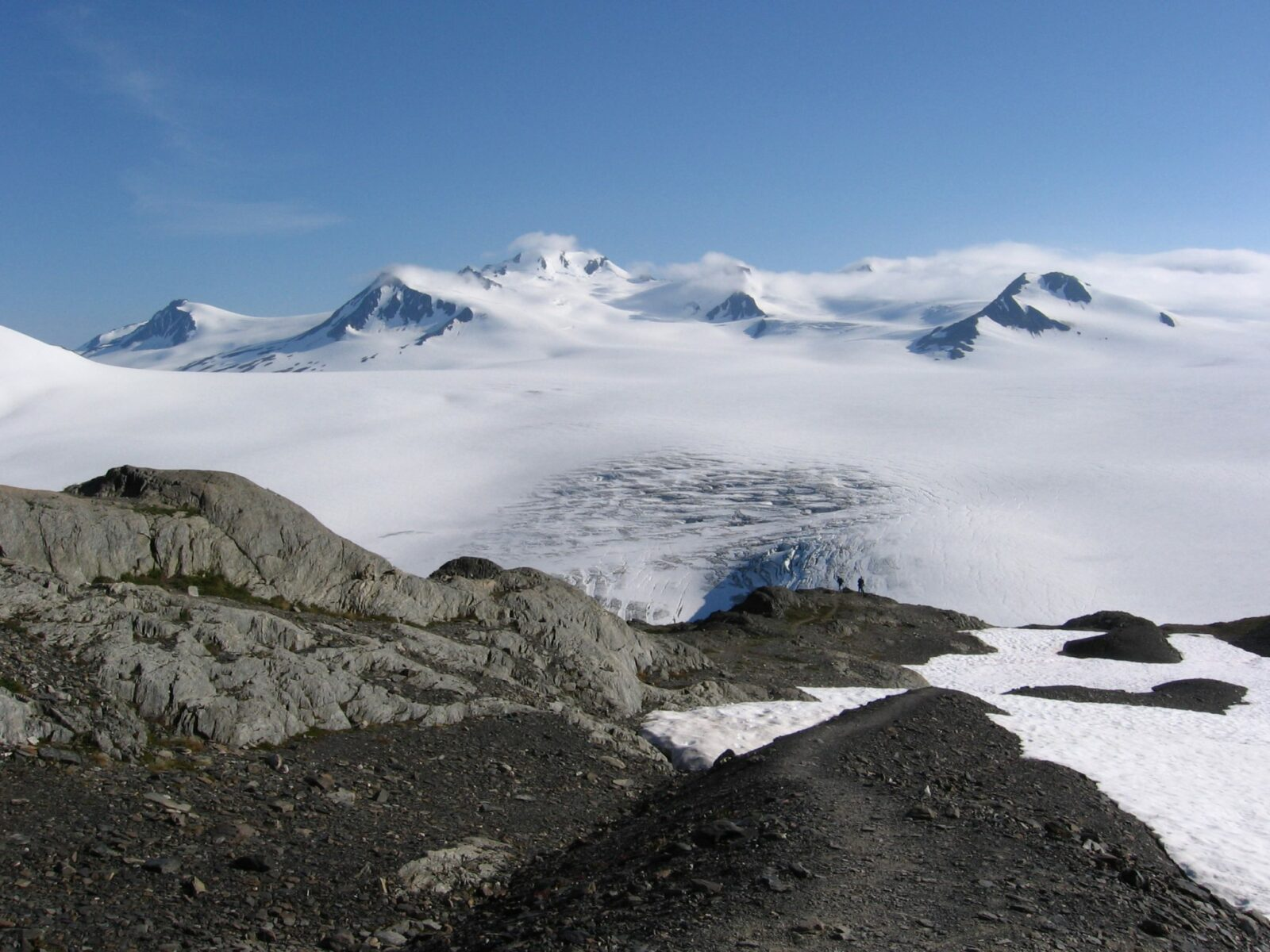 A highlight of Alaska national parks is the Harding Icefield hike. Two hikers in the distance near rocks and a snow field. A glacier in the distance and mountains partially covered in clouds.