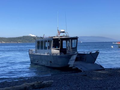 A metal landing boat at a gravel beach ready to load campers and hikers.