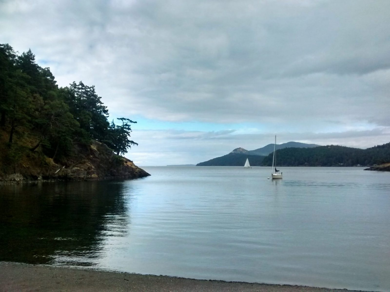 A sailboat at anchor in a small bay. The bay is surrounded by forested hillsides and a gravel beach on a cloudy day