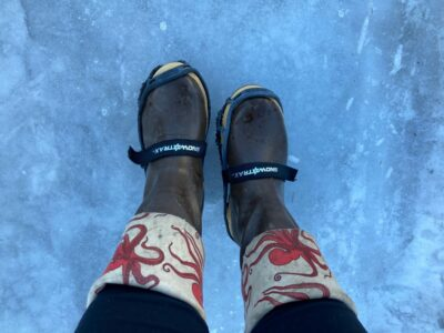 A person's brown rubber boots with an octopus print around the cuff with microspikes attached to the boots. The boots are standing on ice.