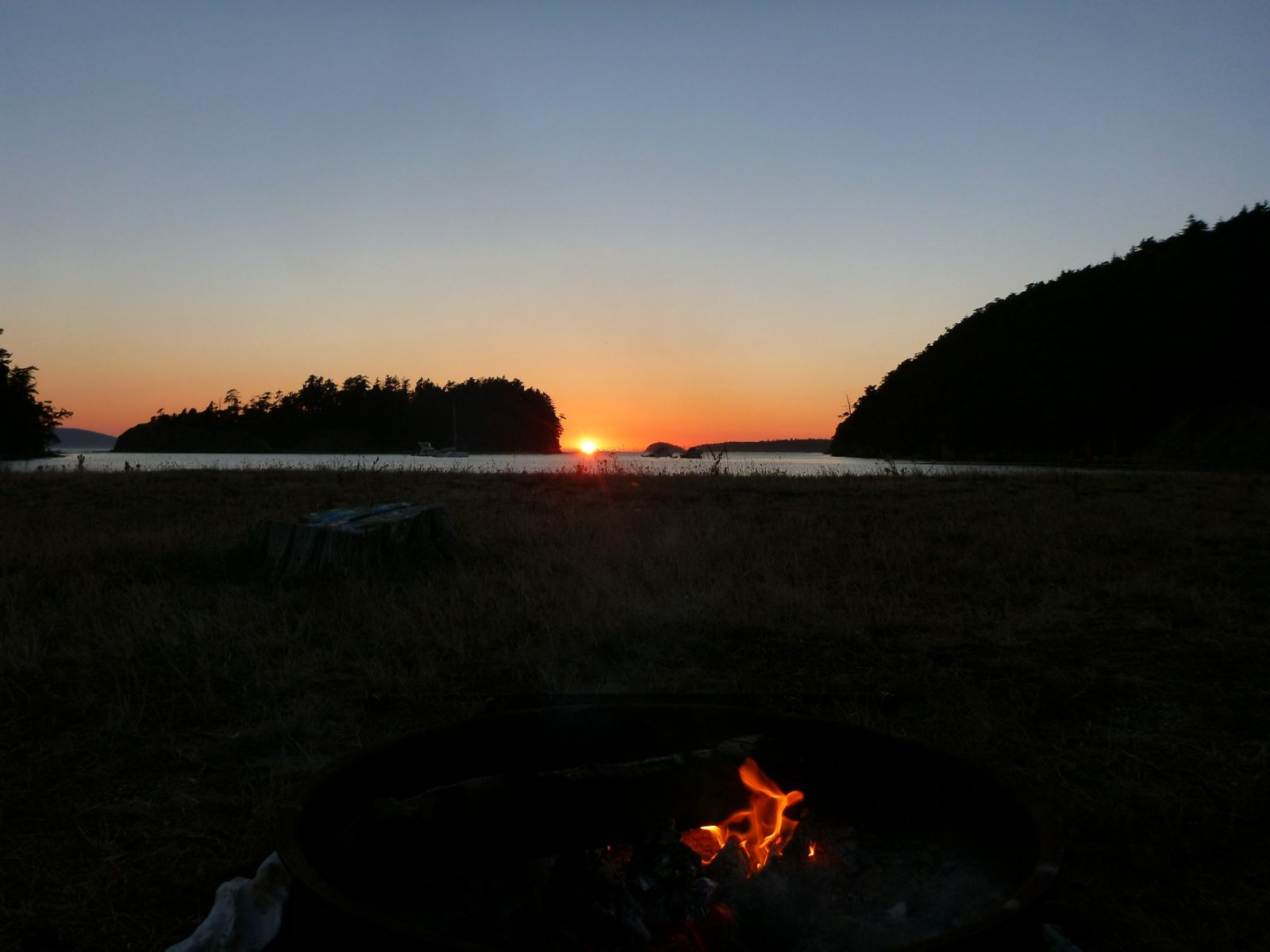 A sunset between distant islands and a campfire in the foreground, camping in the san juan islands