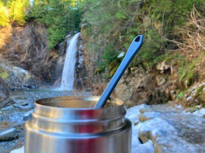A close up of a thermos with hot food and a spoon. Franklin Falls is in the background. There is ice and snow around on the trail.