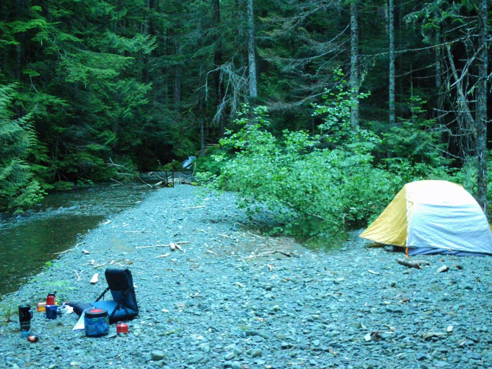 A gravel bar next to a creek in an evergreen tree forest. There is a yellow and white tent set up on the gravel and camping equipment for cooking dinner nearby.