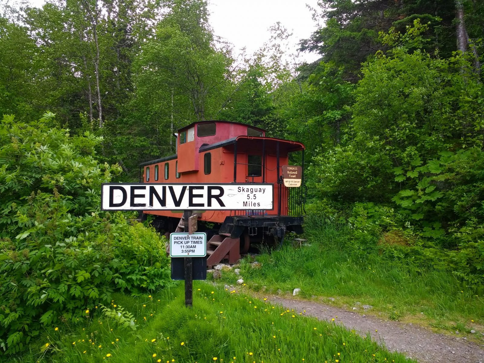 """A red train caboose next to a trail. A railroad sign says """"Denver"""" in the foreground. The sign and caboose are surrounded by green forest. For a unique camping experience in Alaska you can sleep in the caboose"""
