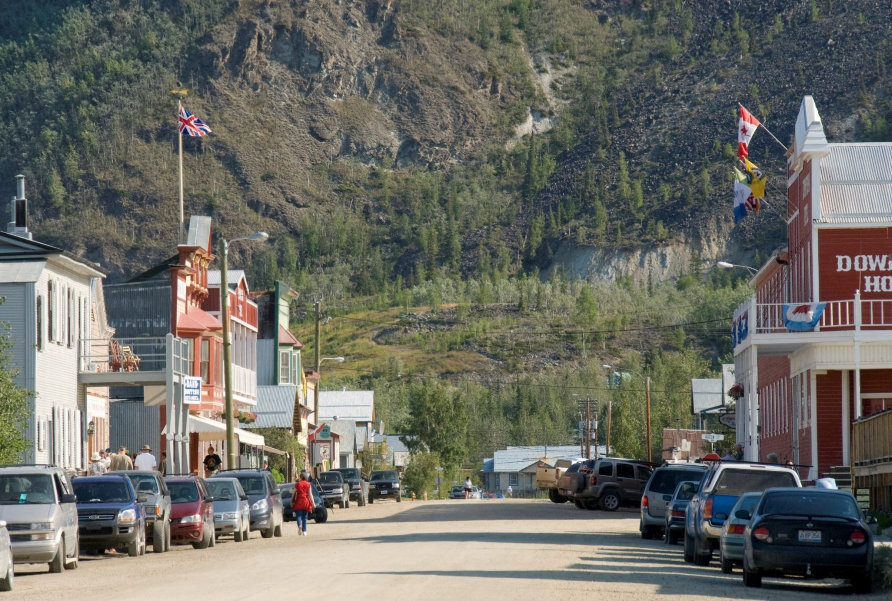 A gravel street in a small town lined with parked cars. The buildings are restored historic buildings. In the background in a forested hillside. Walking the historic streets is one of the best things to do in Dawson City