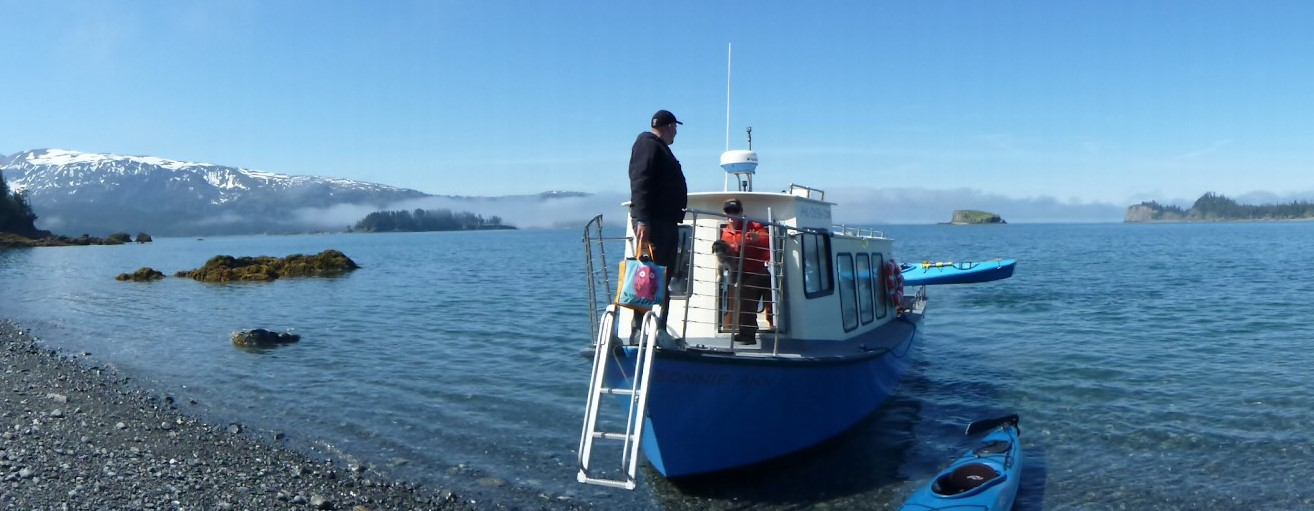 A person coming down a short ladder from a boat that is almost to a gravel beach. There are two blue kayaks near the boat also. The boat has a blue hull and white cabin and room for about 10 people to ride to camp across the bay. There are rocks and forested islands and distant mountains on a sunny day