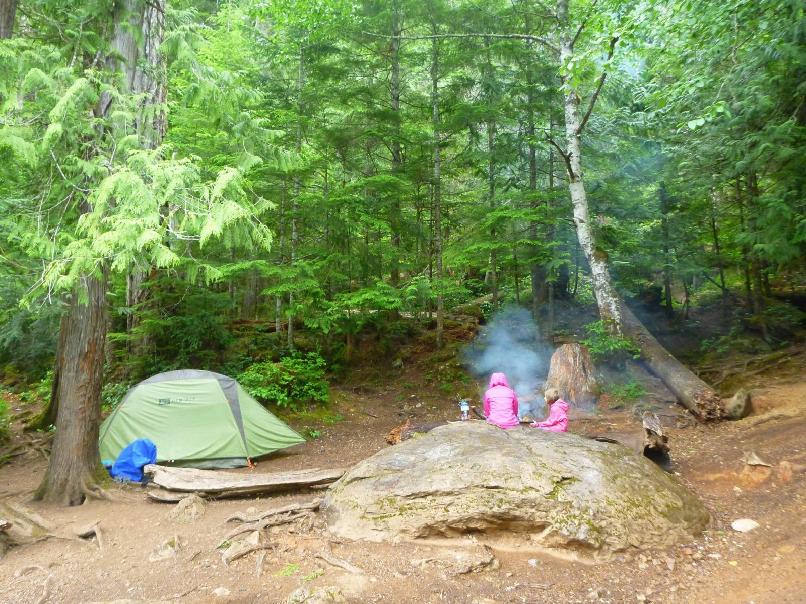An adult and a child wearing pink rain coats sitting next to a campfire. There is a big boulder next to them and a green tent. The campsite is surrounded by trees.