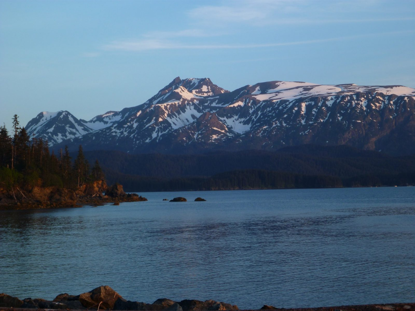 Camping in Alaska in Kachemak Bay State Park. A high mountain with some snow rises above a protected bay surrounded by evergreen trees. It's late evening and teh sun is about to set
