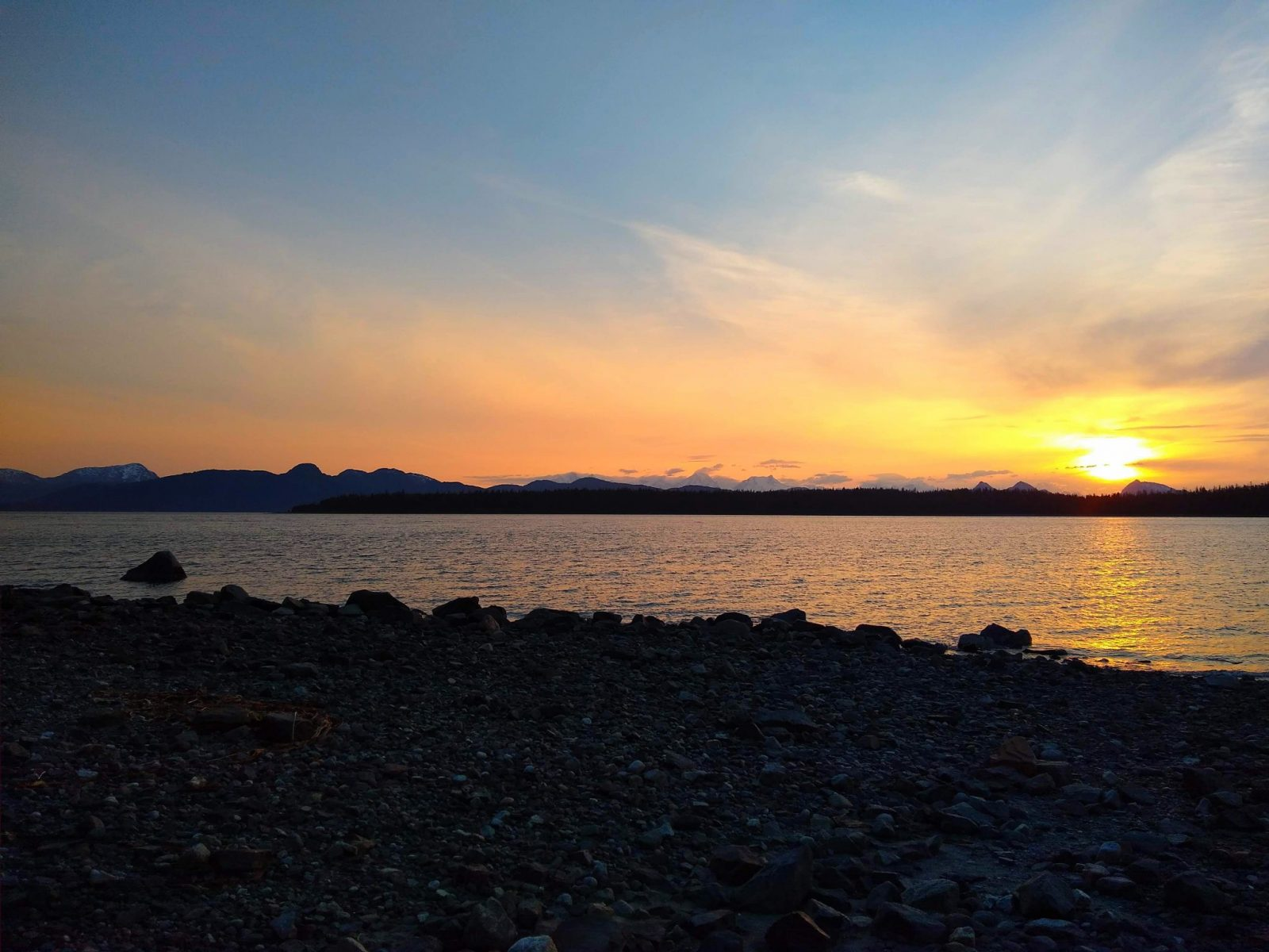 Sunset behind distant mountains across the bay from a rocky beach in the Bartlett Cove Campground in Glacier Bay National Park