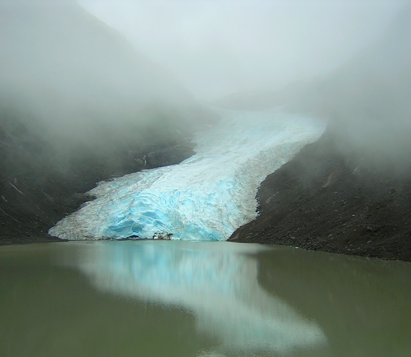 The toe of a glacier at the edge of a lake. The glacier is between two sides of a rocky hillside. It's a foggy day