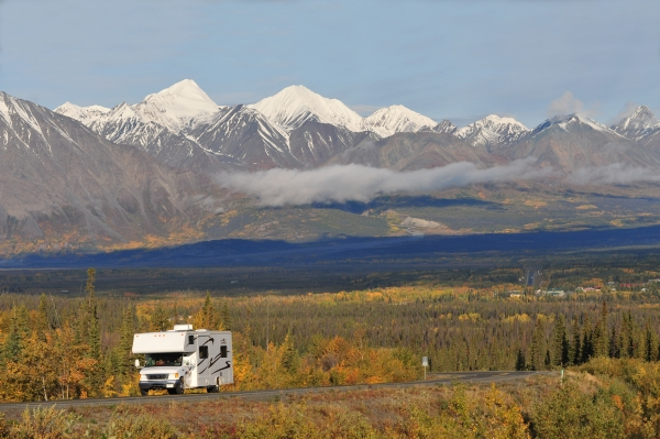 The snowcapped St Elias mountain range and forests with some fall color surround an RV on a two lane highway on the drive to alaska
