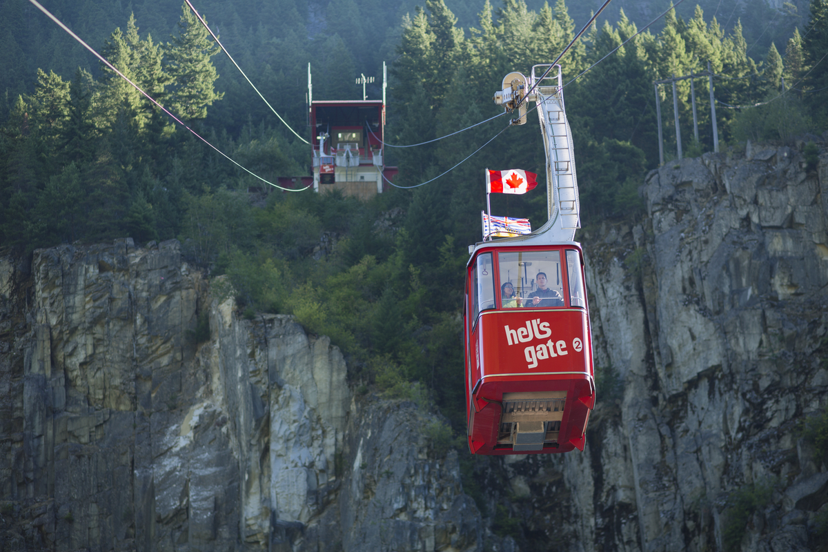 a red aerial tram car on cables going up the side of a rock and forested canyon