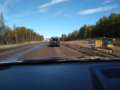 a construction zone on a highway in alaska. The road is graded gravel and there is a small bulldozer next to the road. Trucks and cars are goign through the construction.