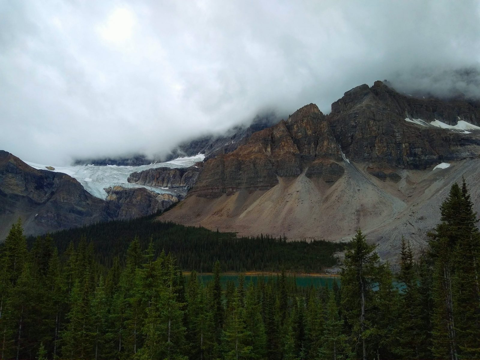mountains with a hanging glacier above a lake and forests on a dark and overcast day