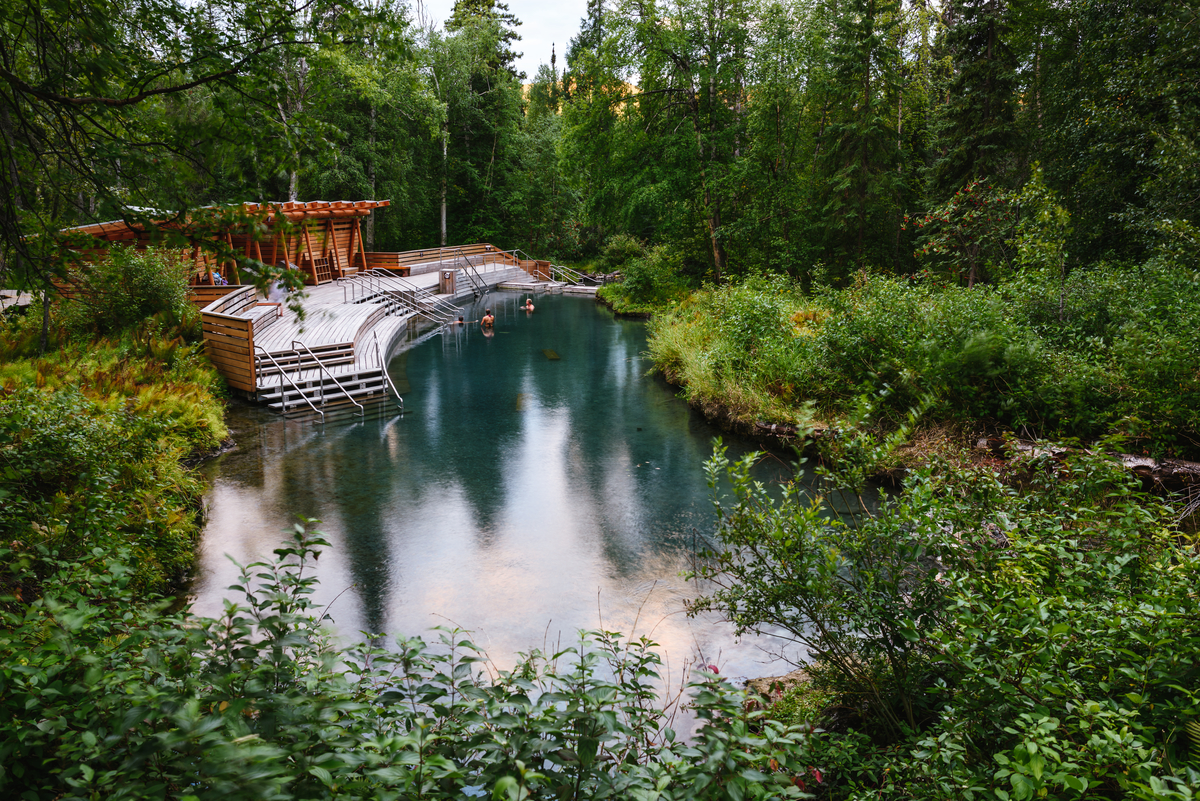 Along the drive to Alaska, Liard Hot Springs is a hot pool with platforms and stairs to help visitors get in the water. There is a wooden building for changing next to the pool. The pool is surrounded by lush green forest and bushes
