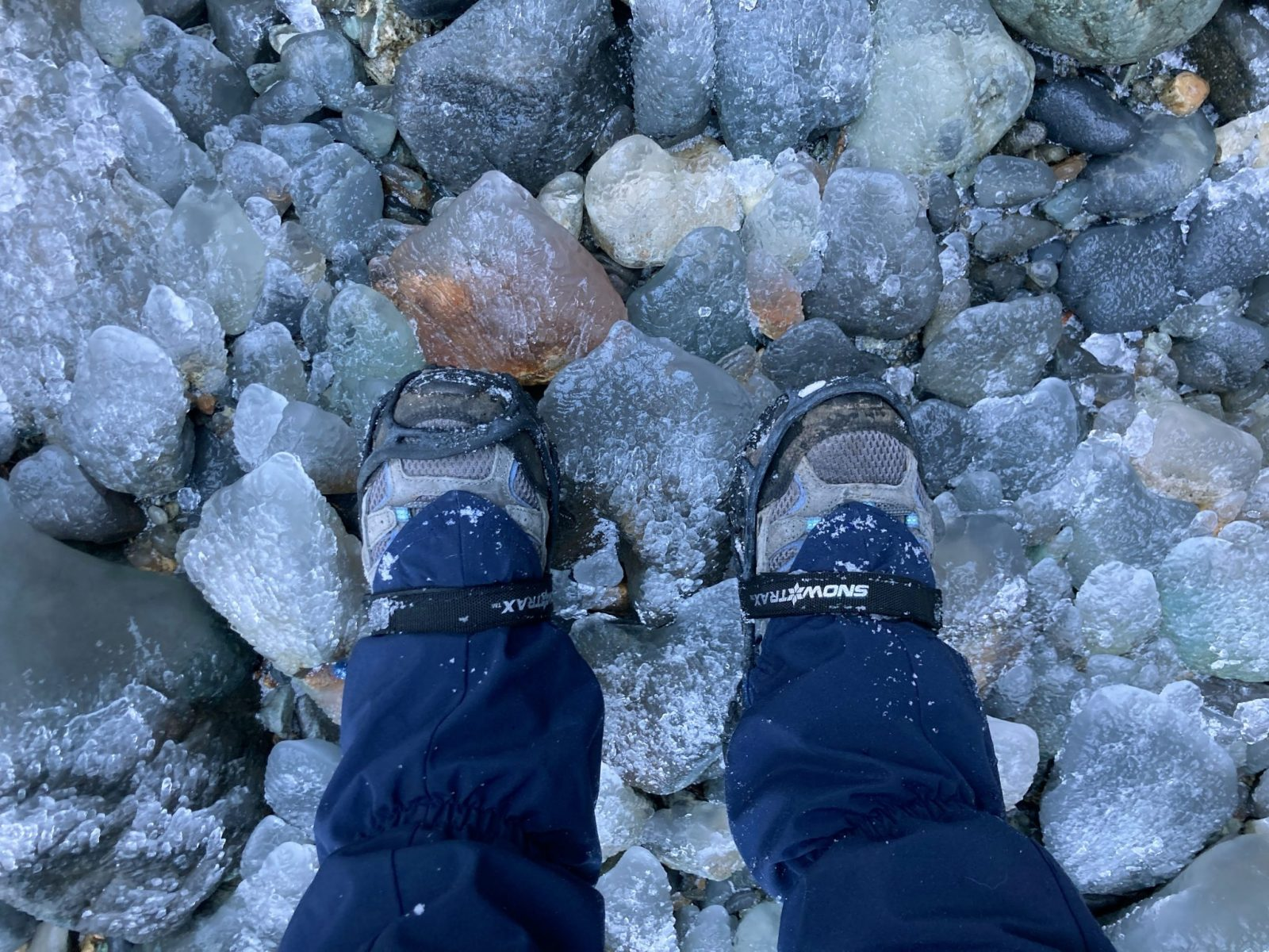 A person's lower legs standing on icy rocks. They are wearing hiking shoes and gaiters and microspikes