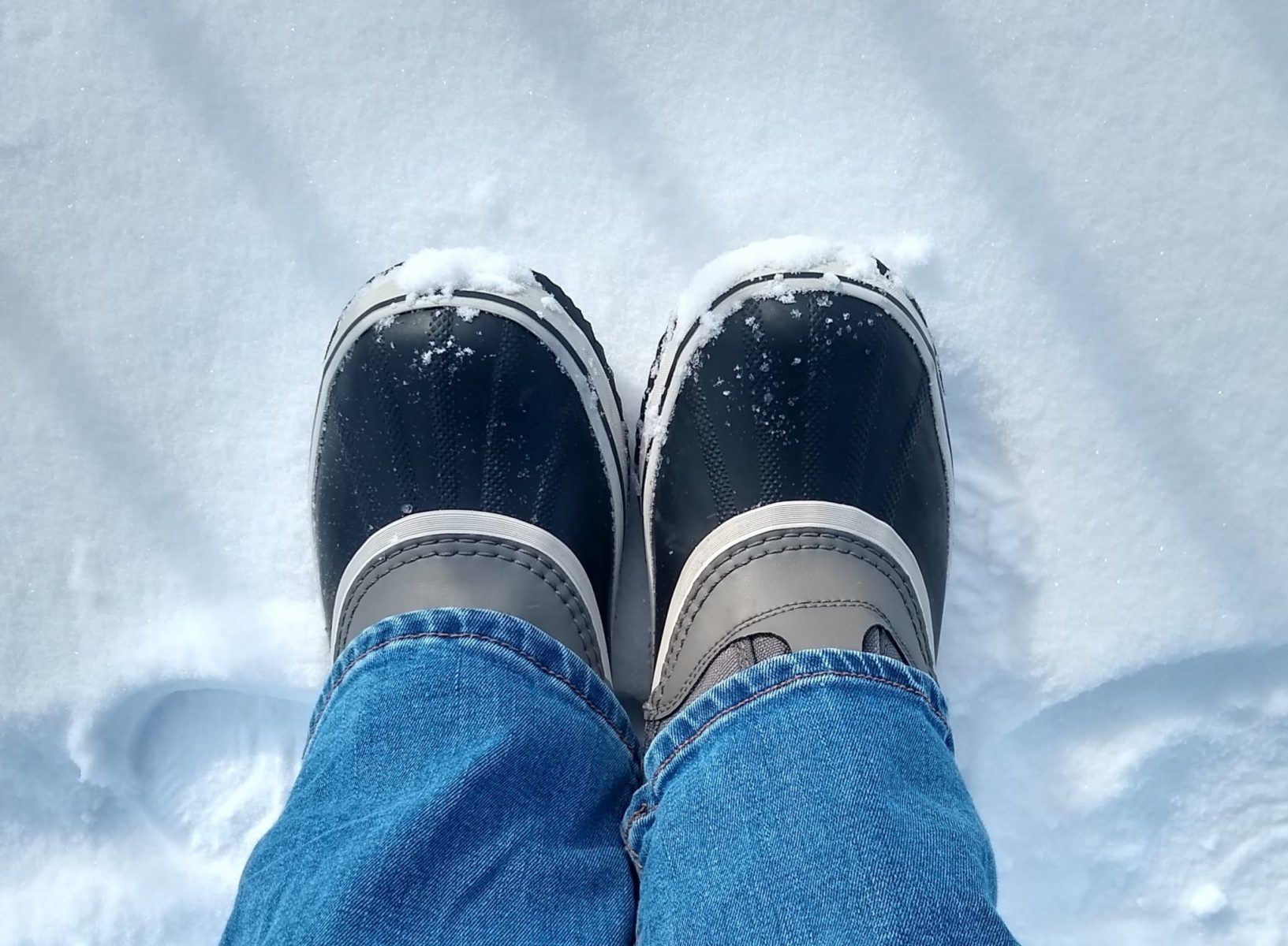 a person's lower legs wearing jeans and rubber snowboots standing in the snow