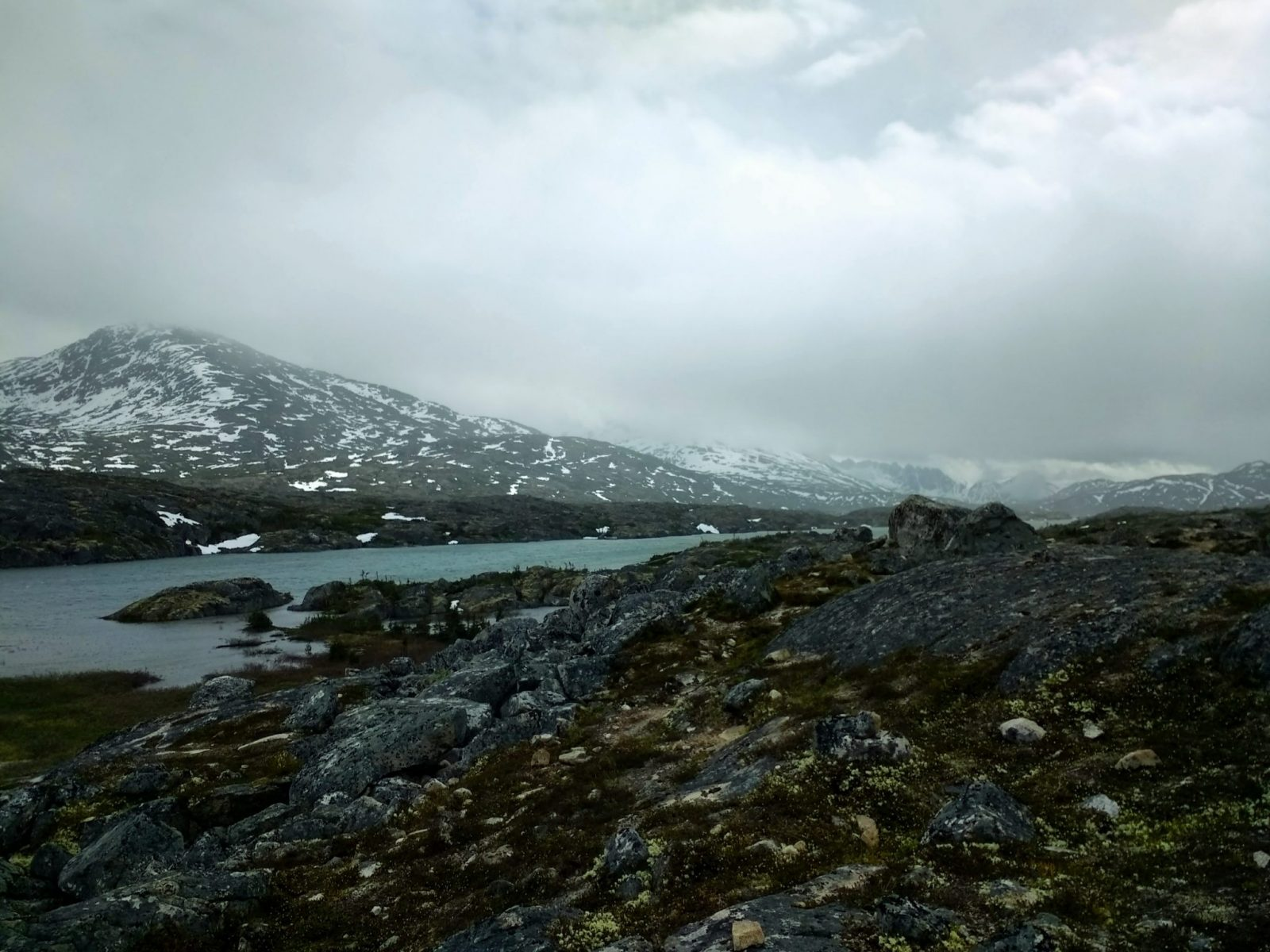 Rocky edges of a lake in a valley holding an alpine lake and surrounded by snowy moutnains on a foggy day